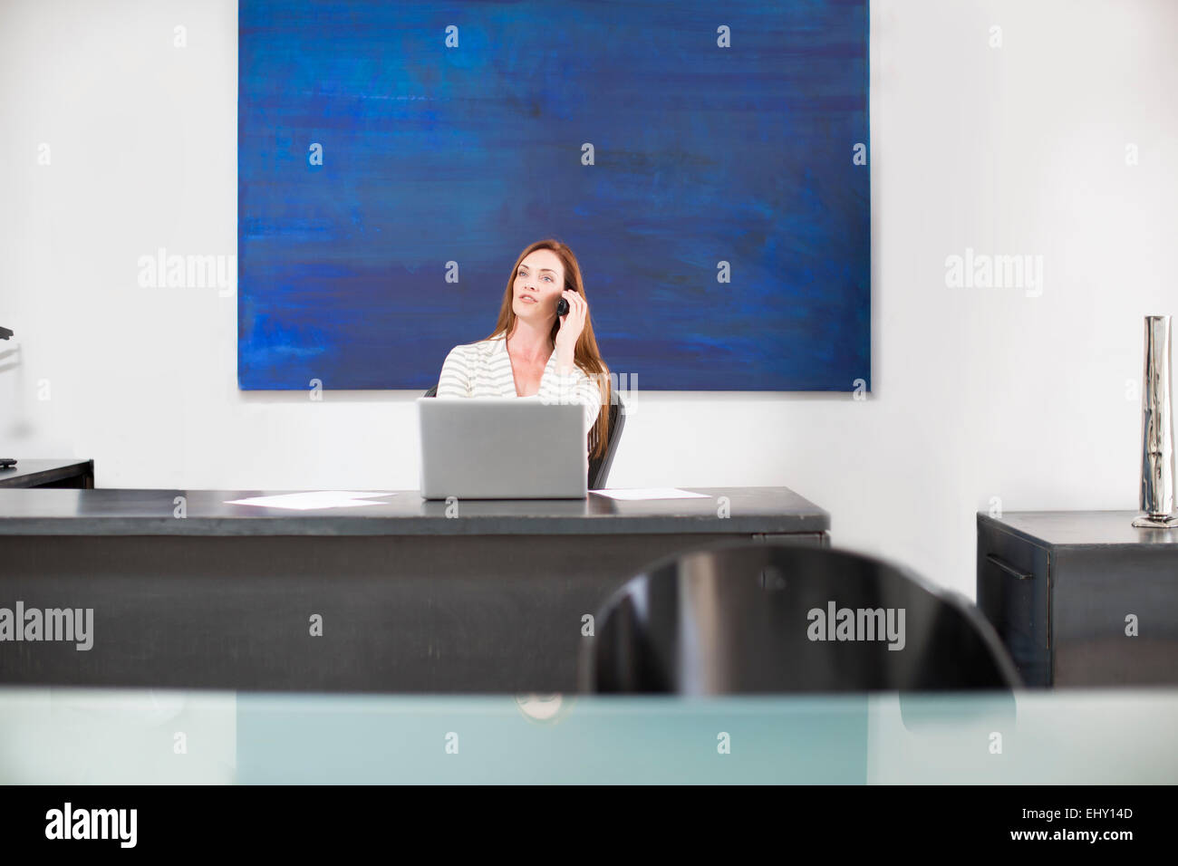 Businesswoman in modern office talking on phone - Stock Image