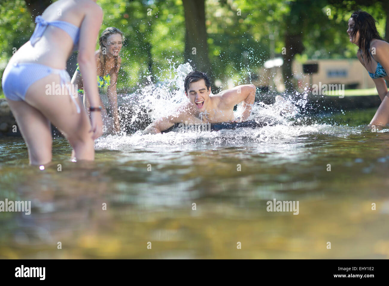 Friends on holiday having fun with inner tube in a pool - Stock Image