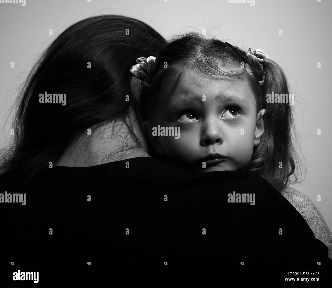 Close between loving supporting mother and sad daughter looking with hope on dark background. Black and white portrait - Stock Image