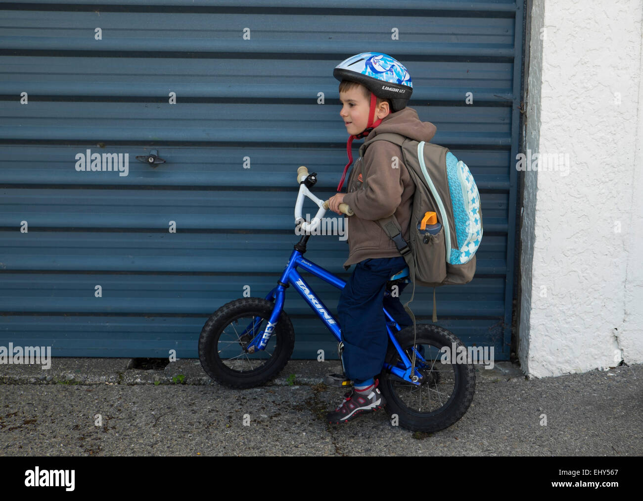 Four year old boy with backpack on bike with helmet - Stock Image