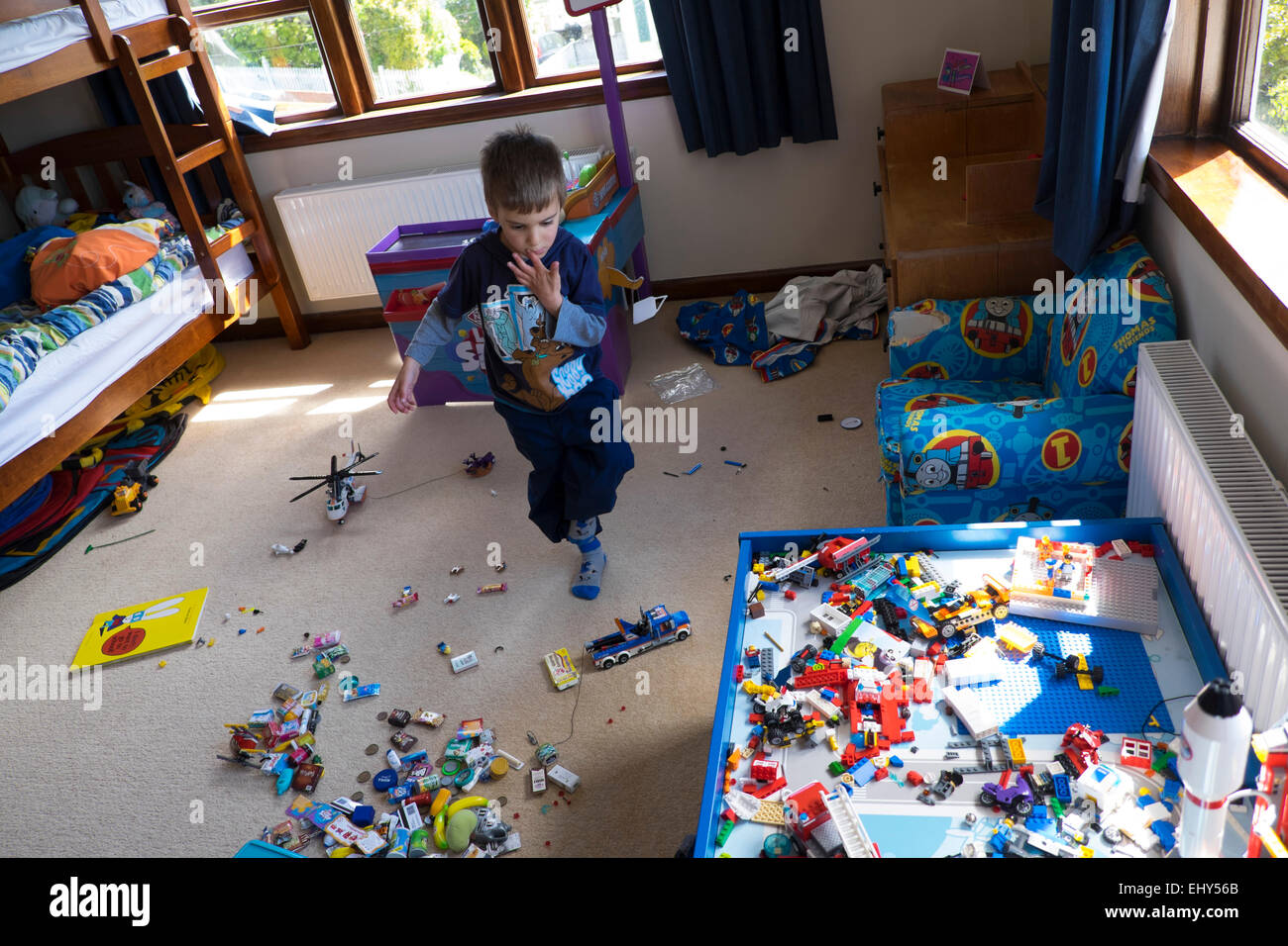 Boy aged four years playing with Lego building blocks in bedroom - Stock Image