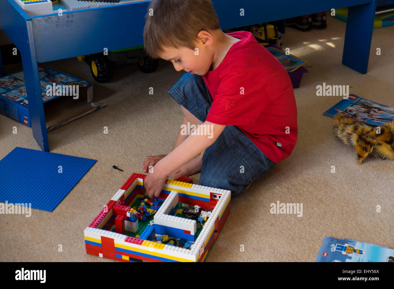Boy aged four years playing with Lego building blocks in bedroom Stock Photo