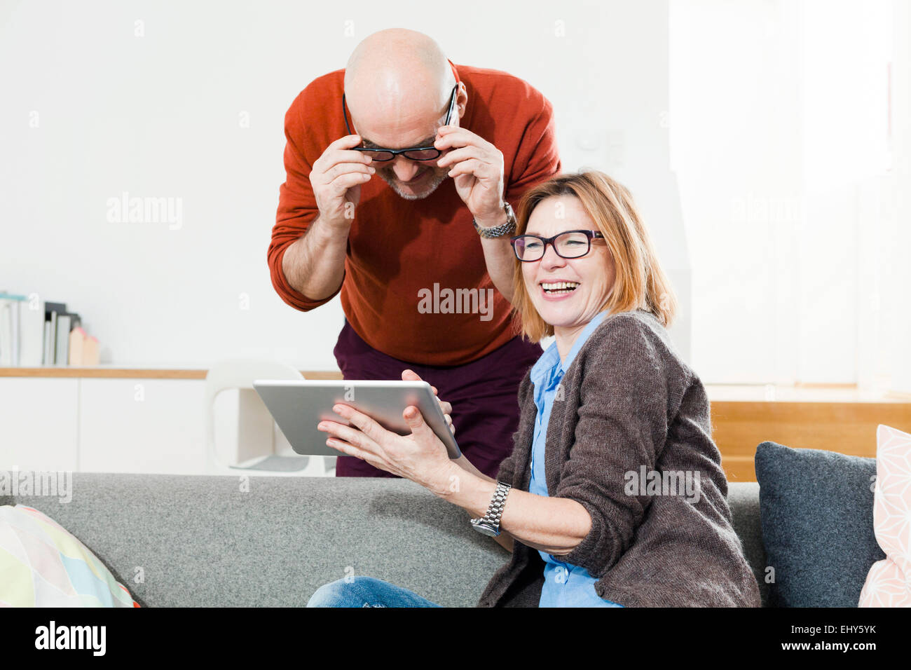 Senior couple using digital tablet at home - Stock Image