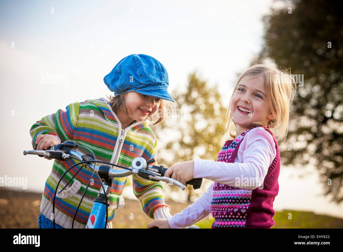 Two girls playing with bicycle - Stock Image