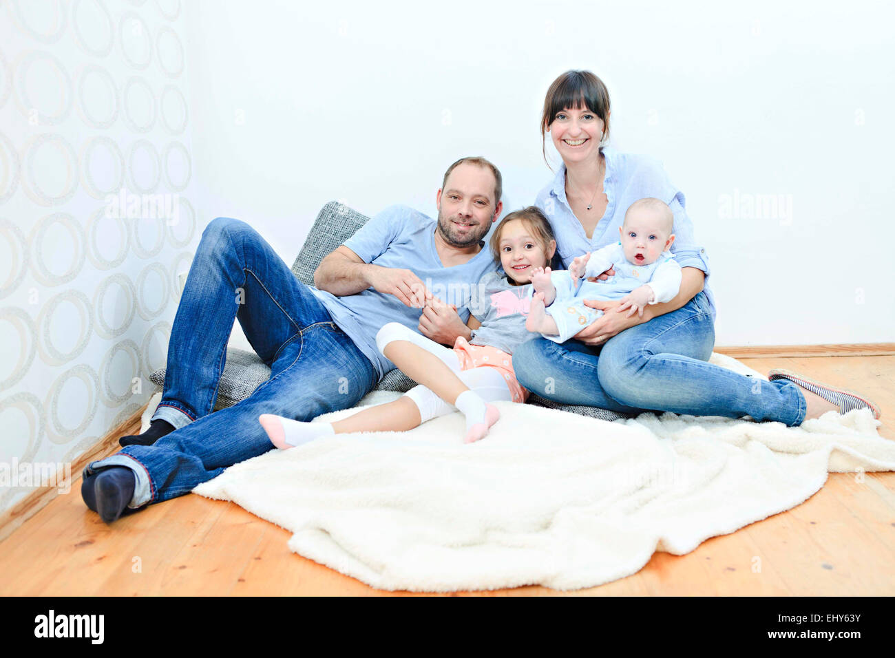 Family at home relaxing on blanket - Stock Image