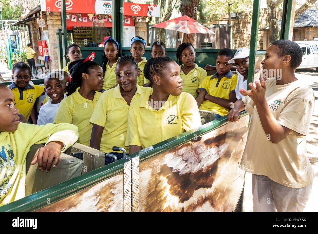 Johannesburg South Africa African Zoo Black teen boy girl student class field trip guide teacher explaining teaching - Stock Image