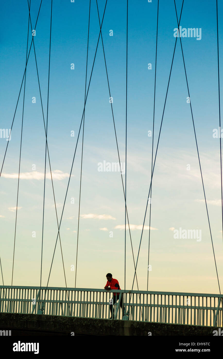 Male runner on bridge takes a break - Stock Image