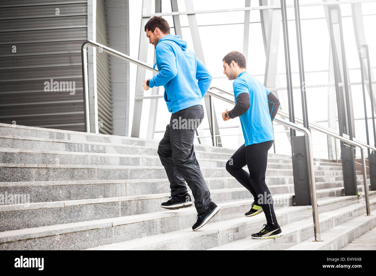 Two male runners warming up on staircase - Stock Image