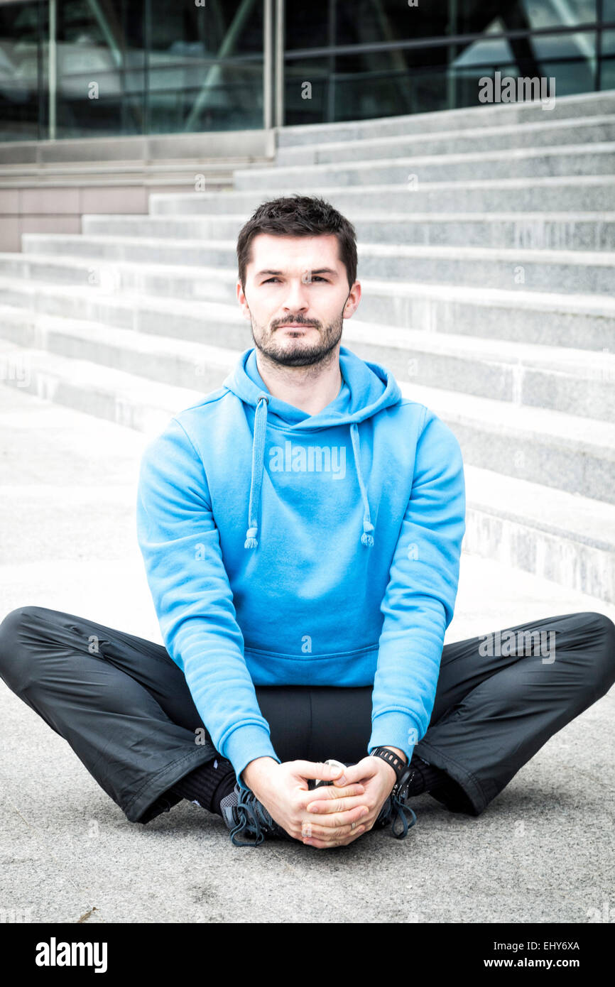 Male runner takes a break sitting cross-legged - Stock Image