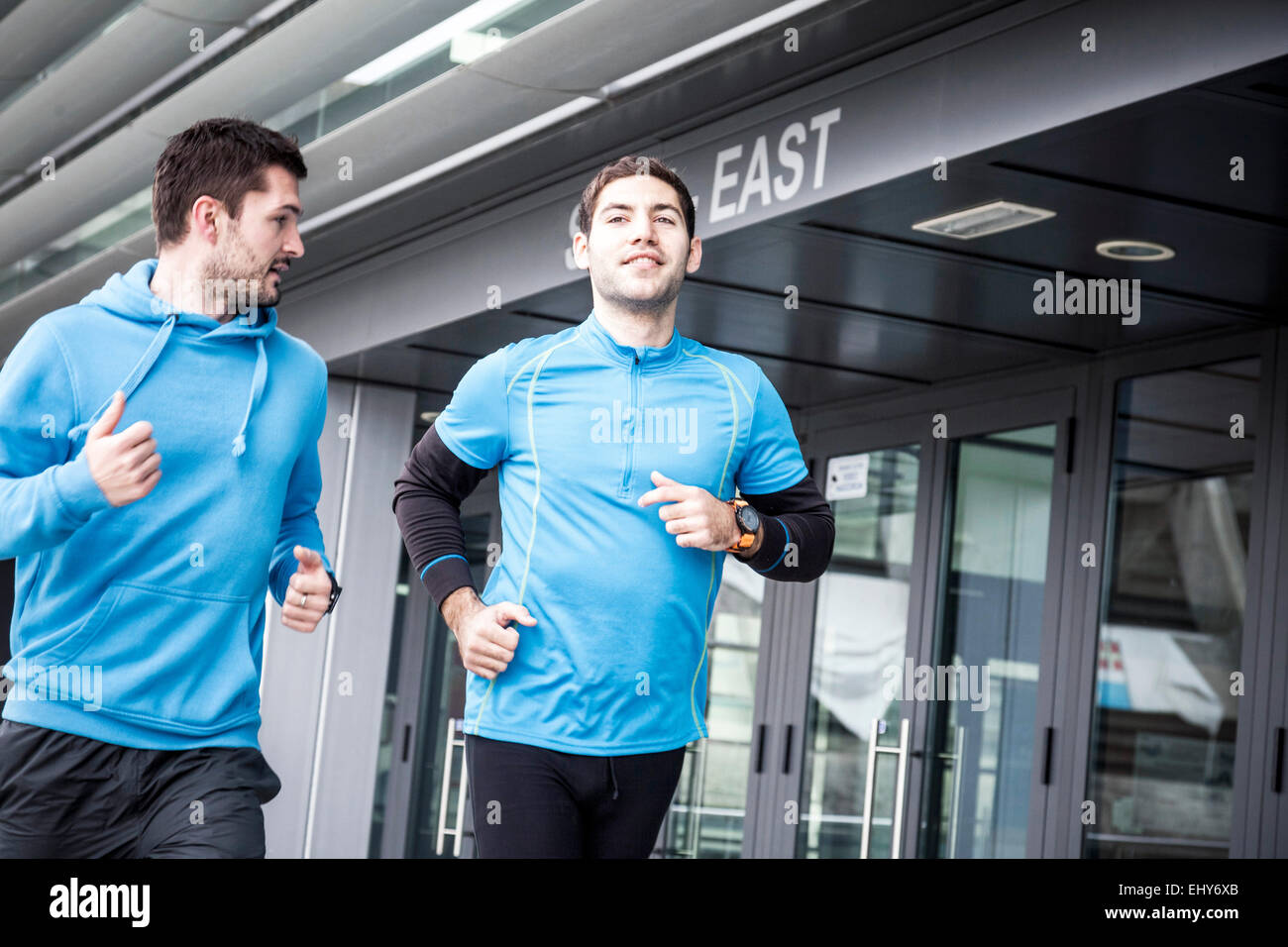 Male runners jogging in city side by side - Stock Image