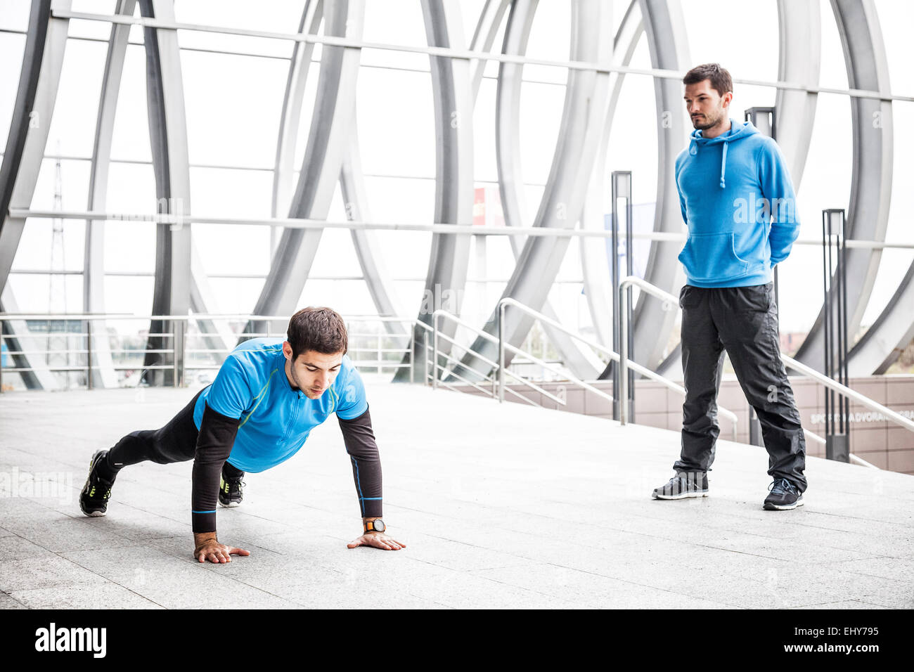 Two male runners doing push-ups in city - Stock Image