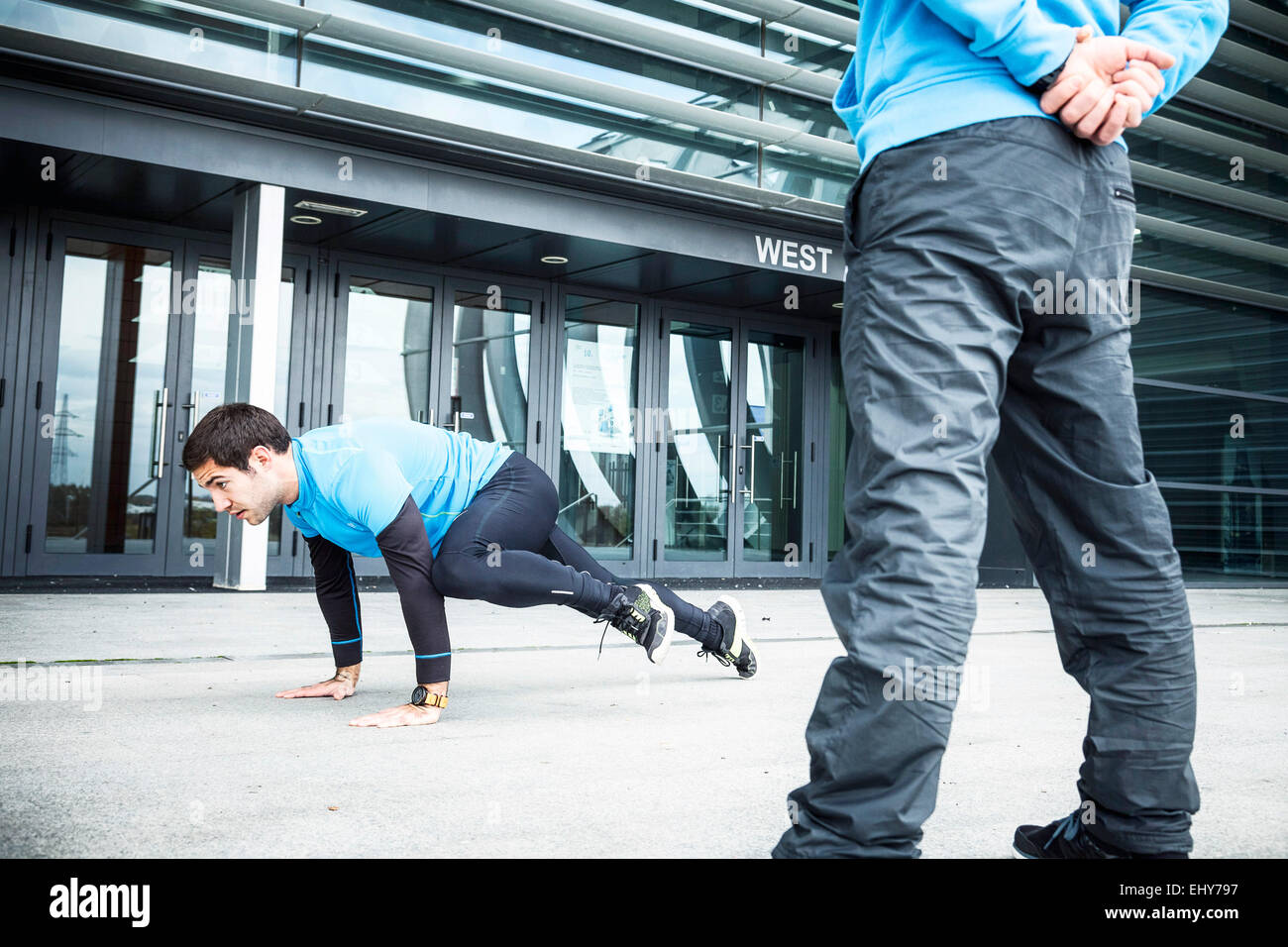 Male runners doing push-ups in city - Stock Image