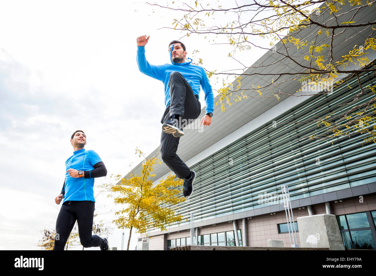 Two male runners jogging and jumping in city - Stock Image
