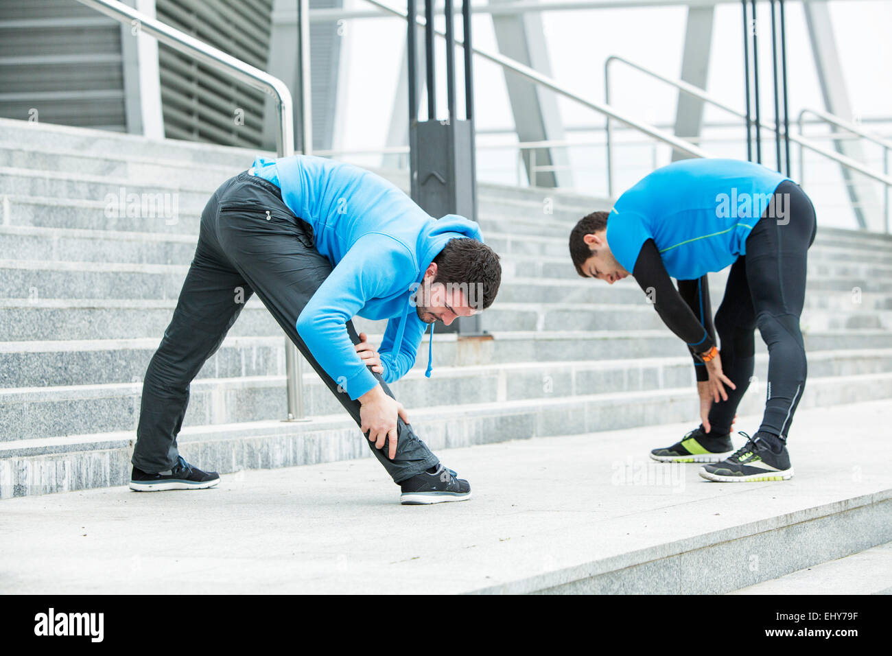 Male runners stretching and warming up together - Stock Image