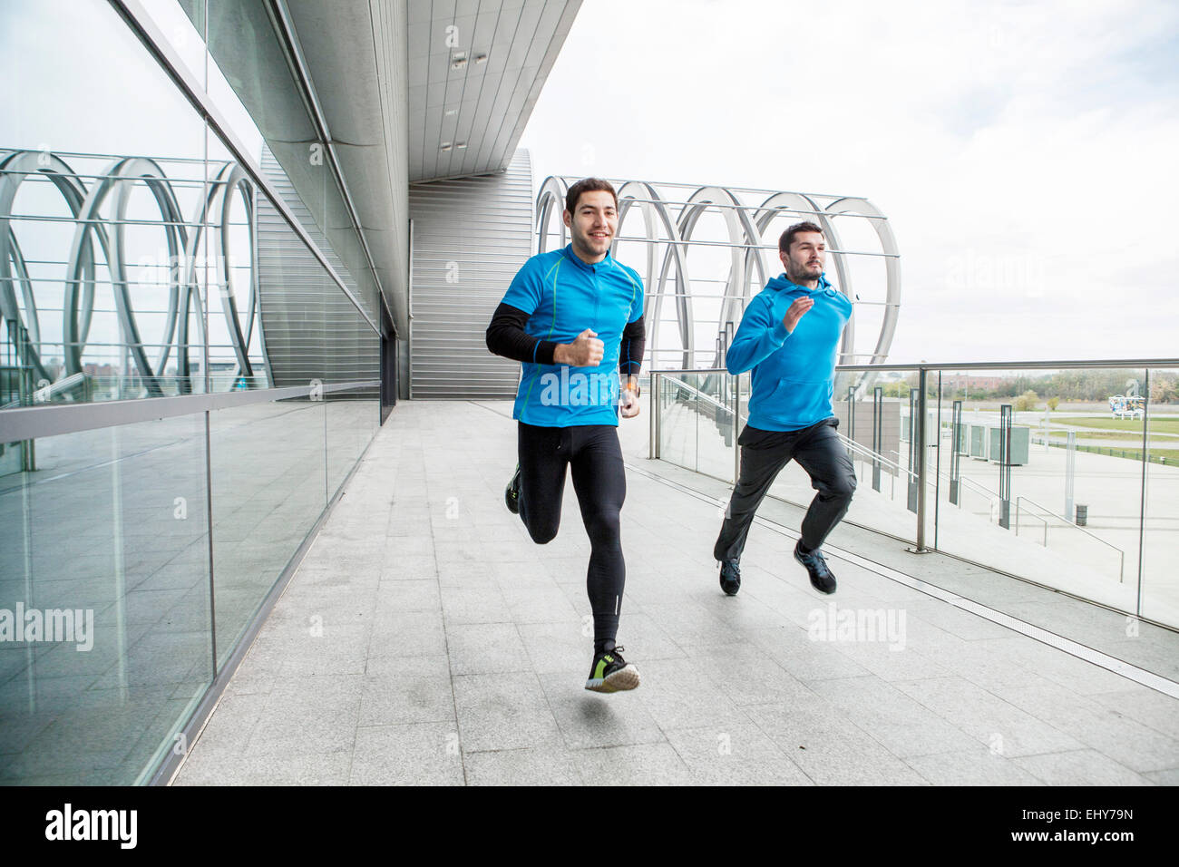 Male runners doing sprint training in city - Stock Image