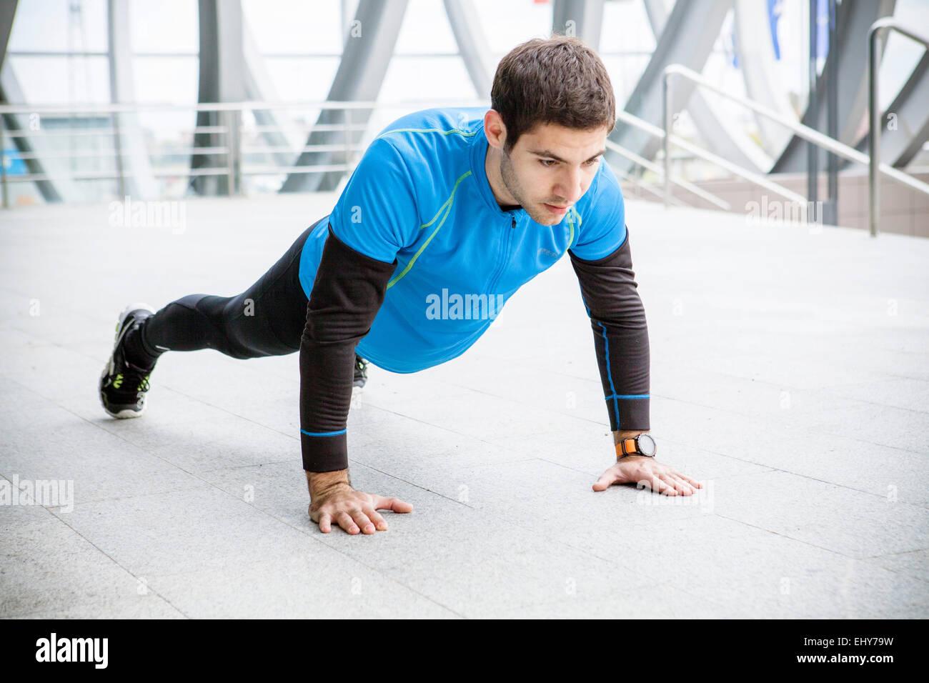 Male runner doing push-ups in city - Stock Image