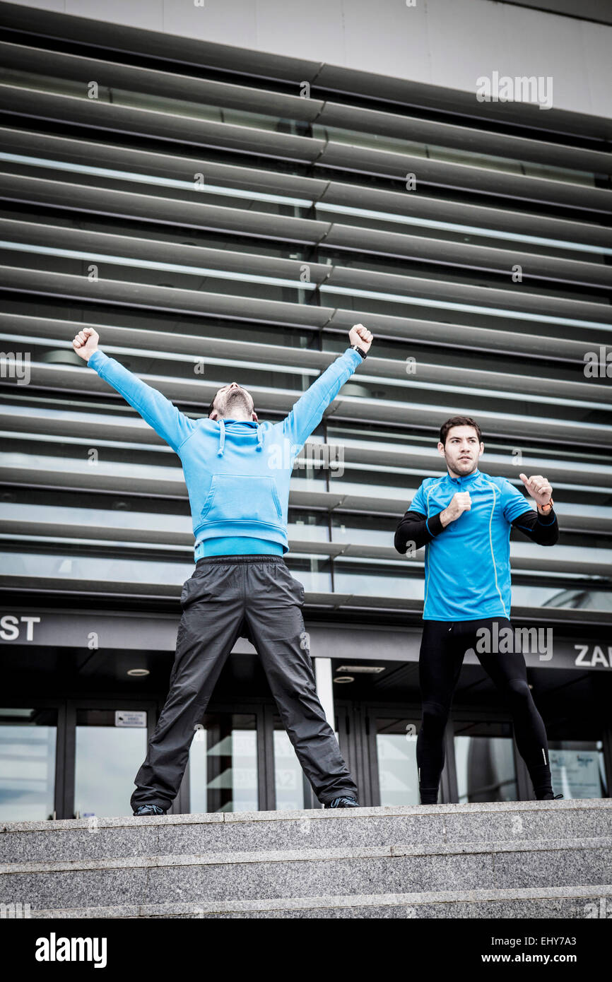 Male runners exercising together in city - Stock Image