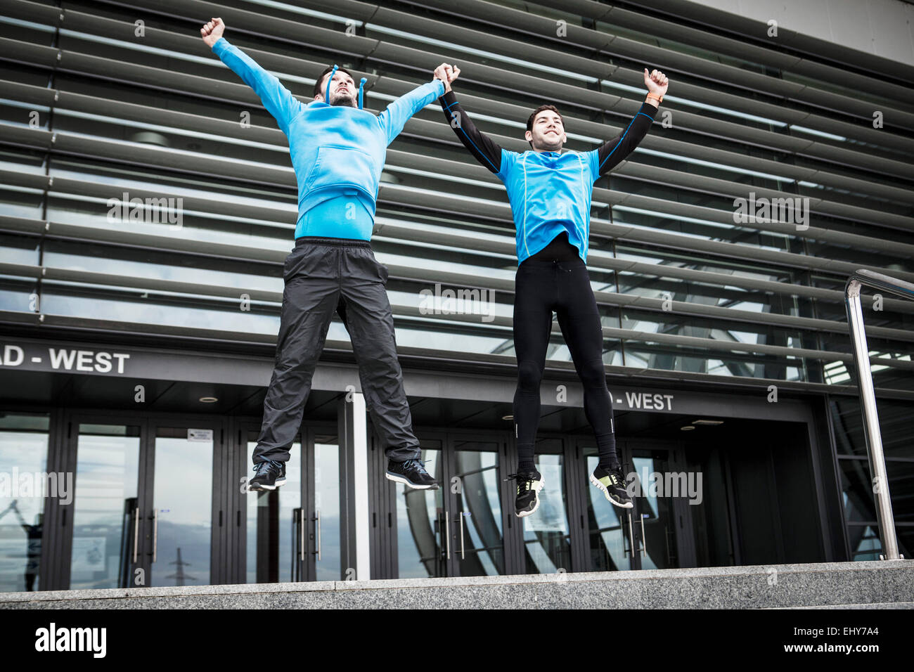 Male runners jumping side by side in city - Stock Image