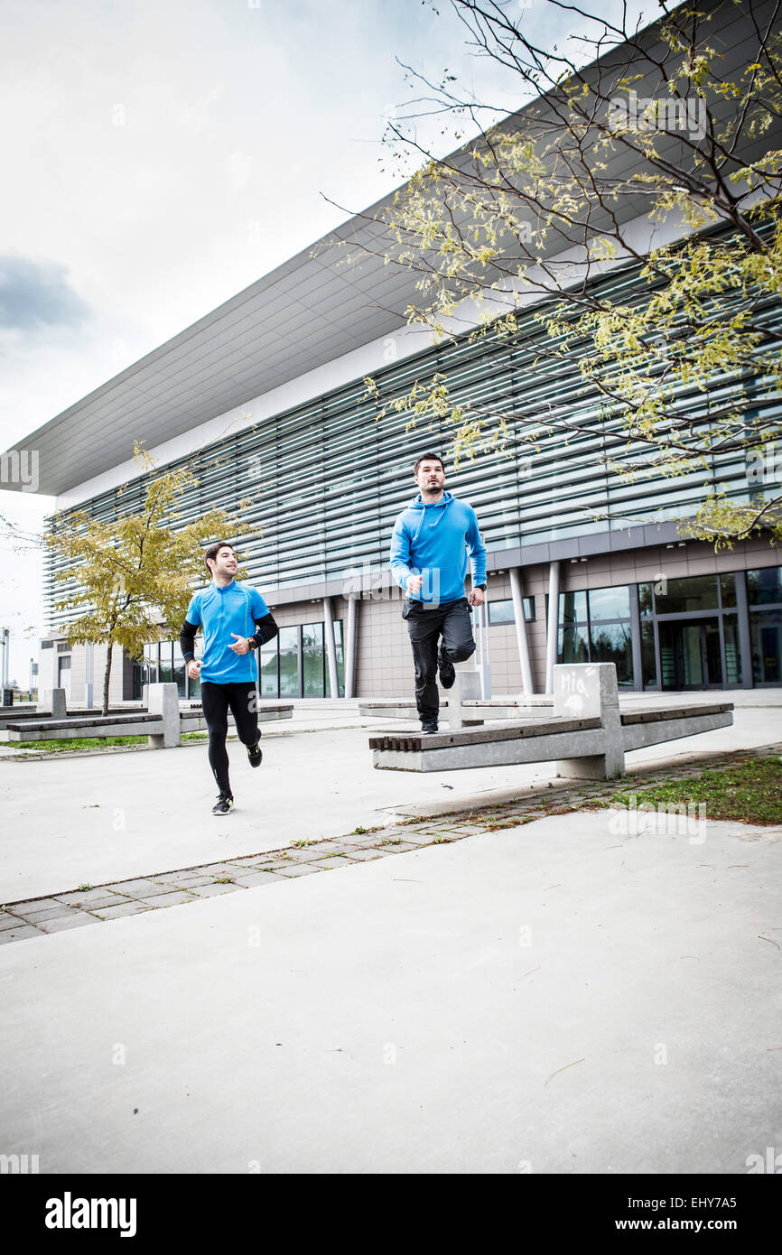 Two male runners jogging together in city - Stock Image