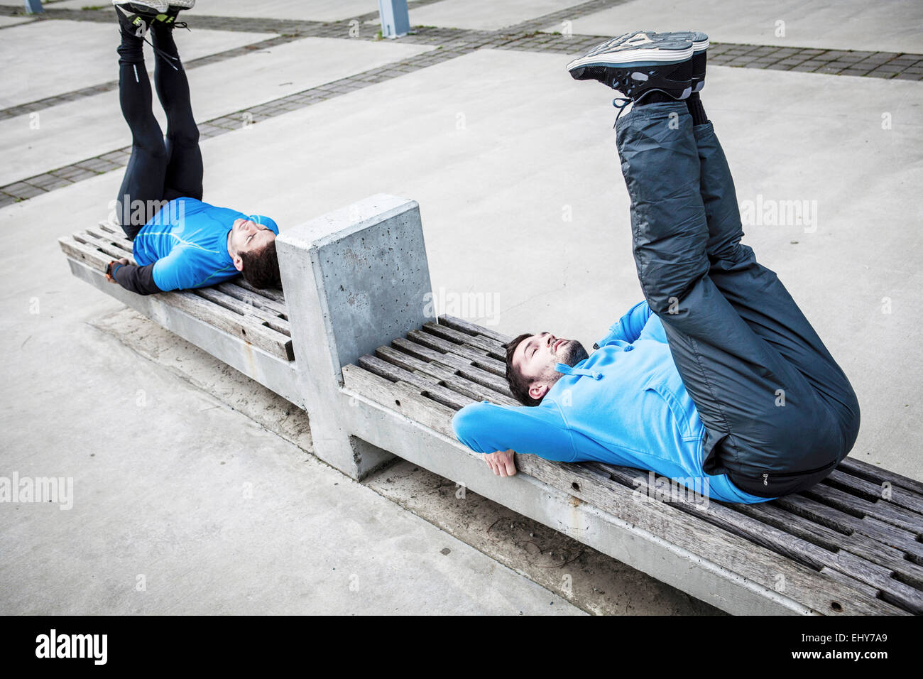 Male runners stretching and warming up in city - Stock Image