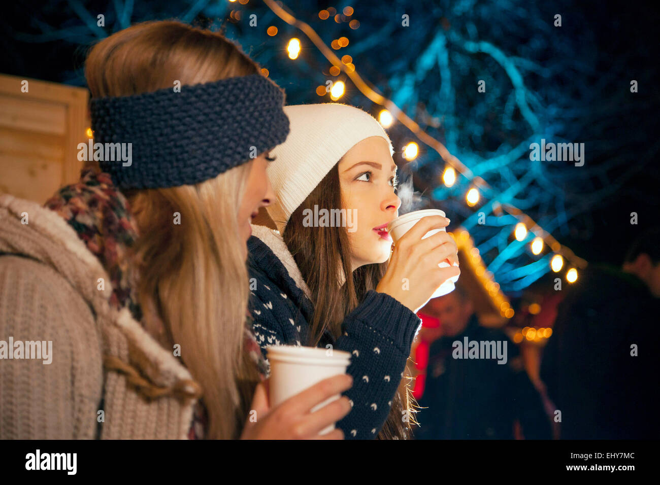Two women drinking punch at Christmas Market - Stock Image