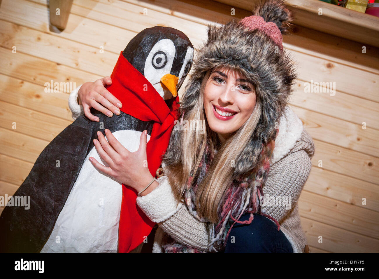 Young woman posing with penguin figurine - Stock Image