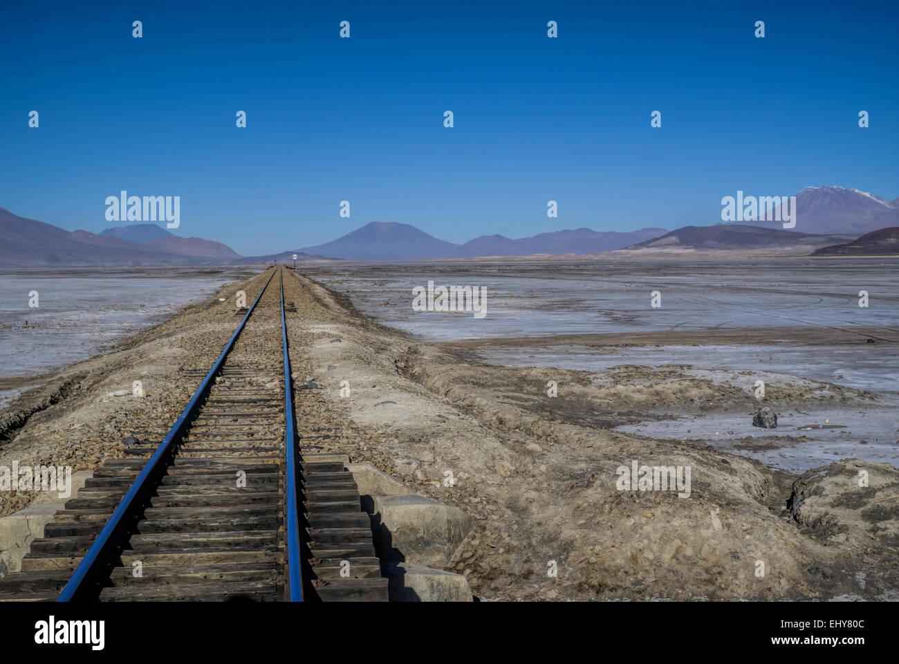 Rail tracks in desert covered by white salt in Salar de Uyuni in Bolivia - Stock Image
