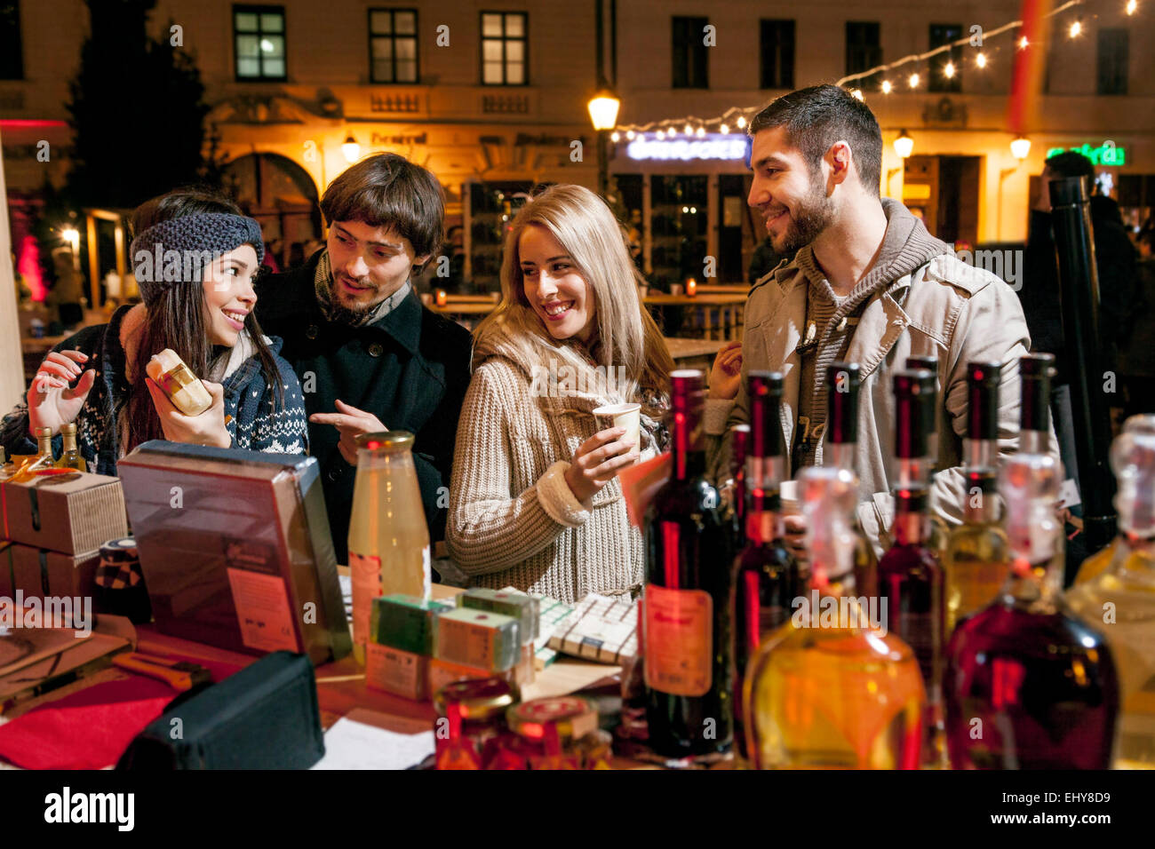 Group of friends by stall at Christmas Market - Stock Image