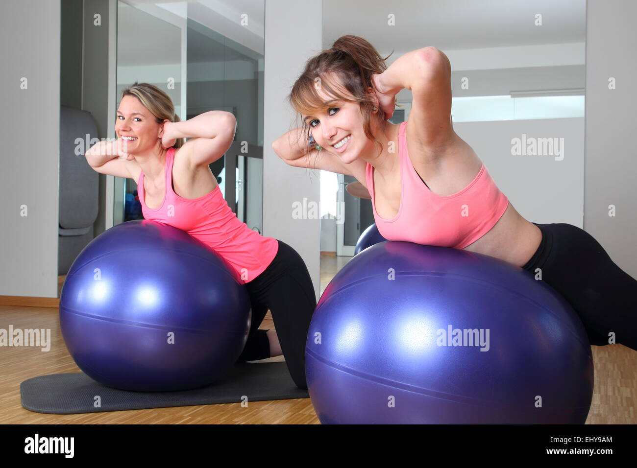 Two women in a fitness center together on a Fitness Ball - Stock Image
