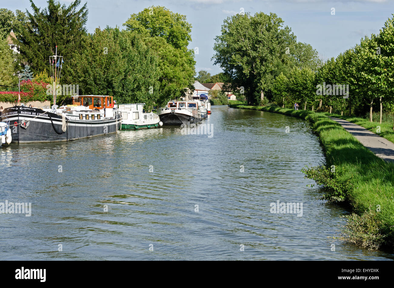 On the left, boats are tied up at the Fragnes marina; on the right, the old towpath has become the Voie Verte. Canal - Stock Image