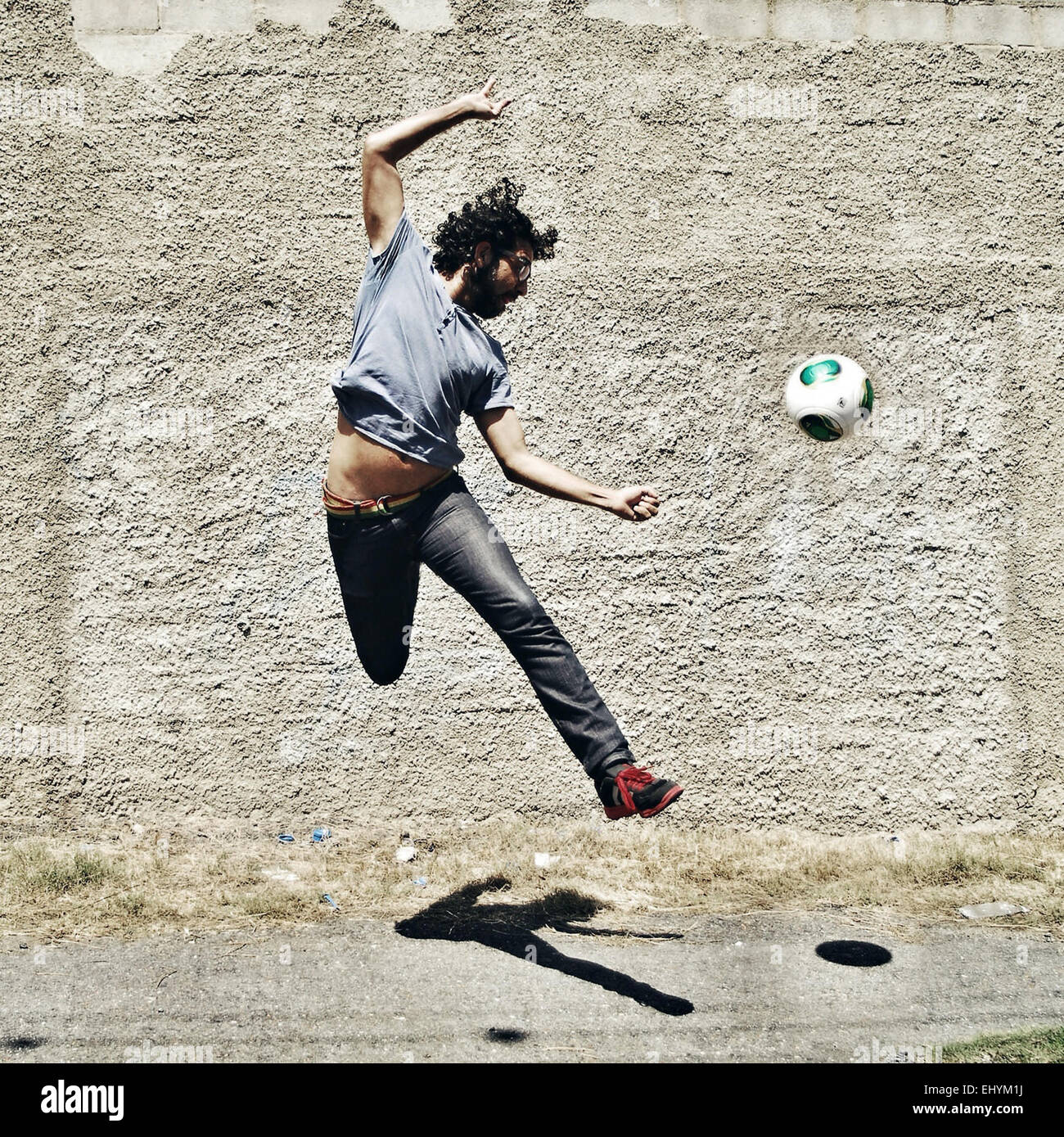 Man playing football in the street Stock Photo