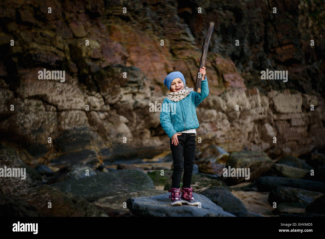 ca85a4351 Girl standing on rock at the beach holding a stick - Stock Image