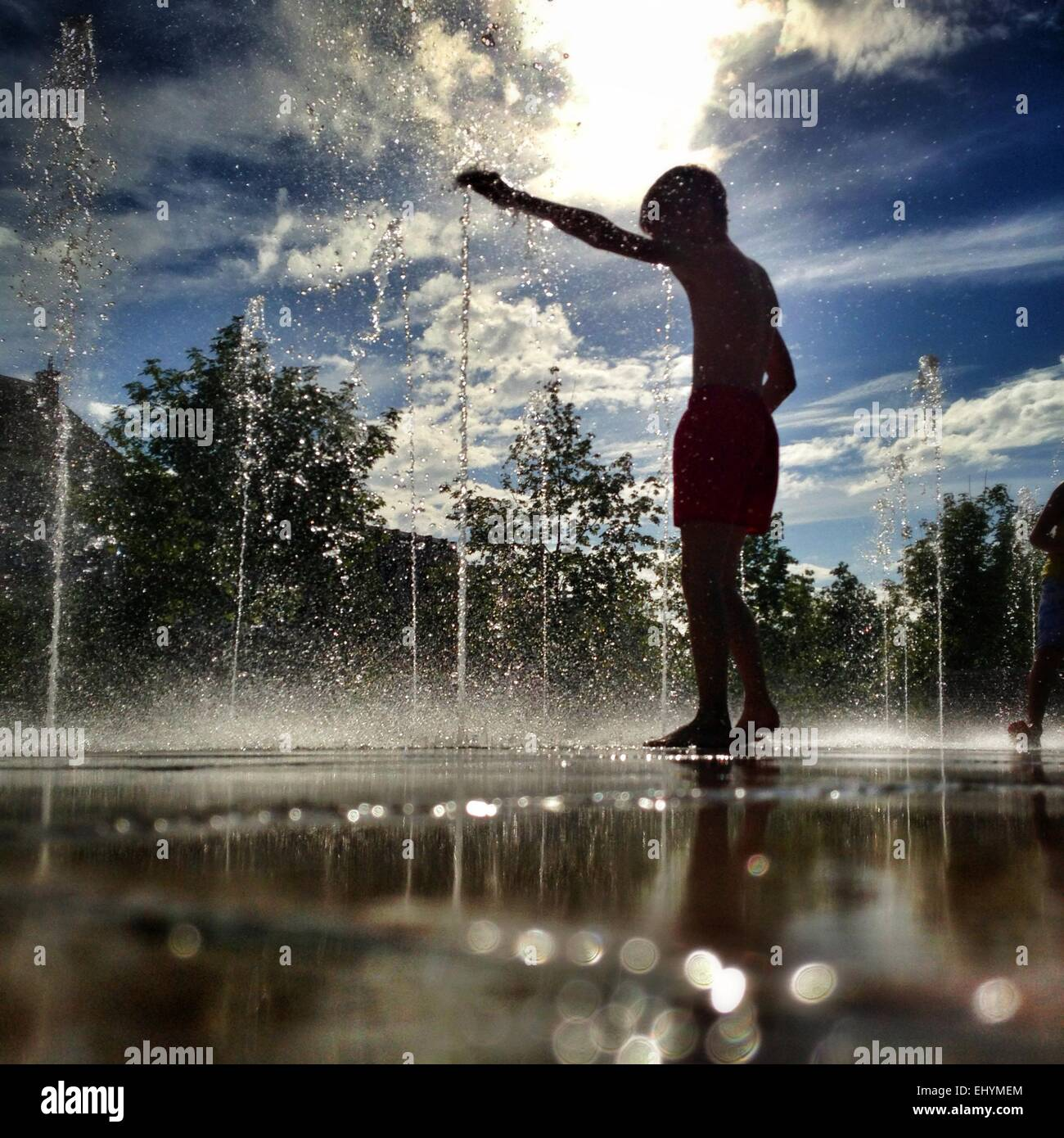 Silhouette of a boy standing in a water fountain, Niort, France - Stock Image
