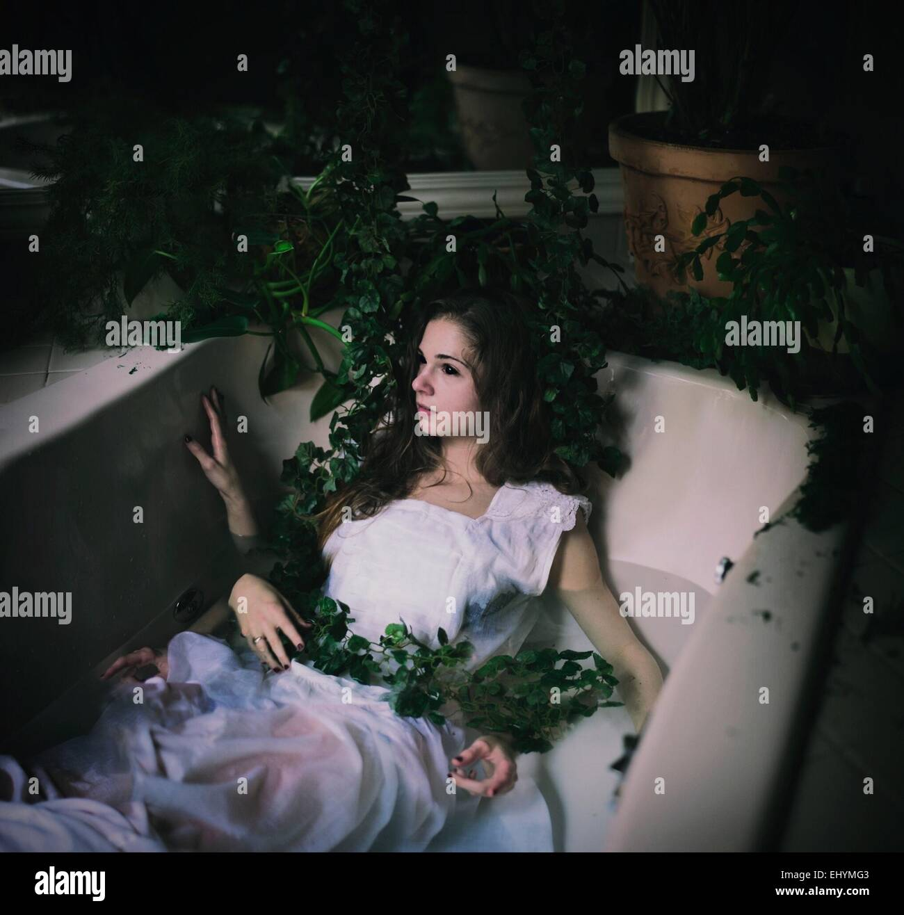 Young woman lying in a bath tub with lots of hands and vines - Stock Image
