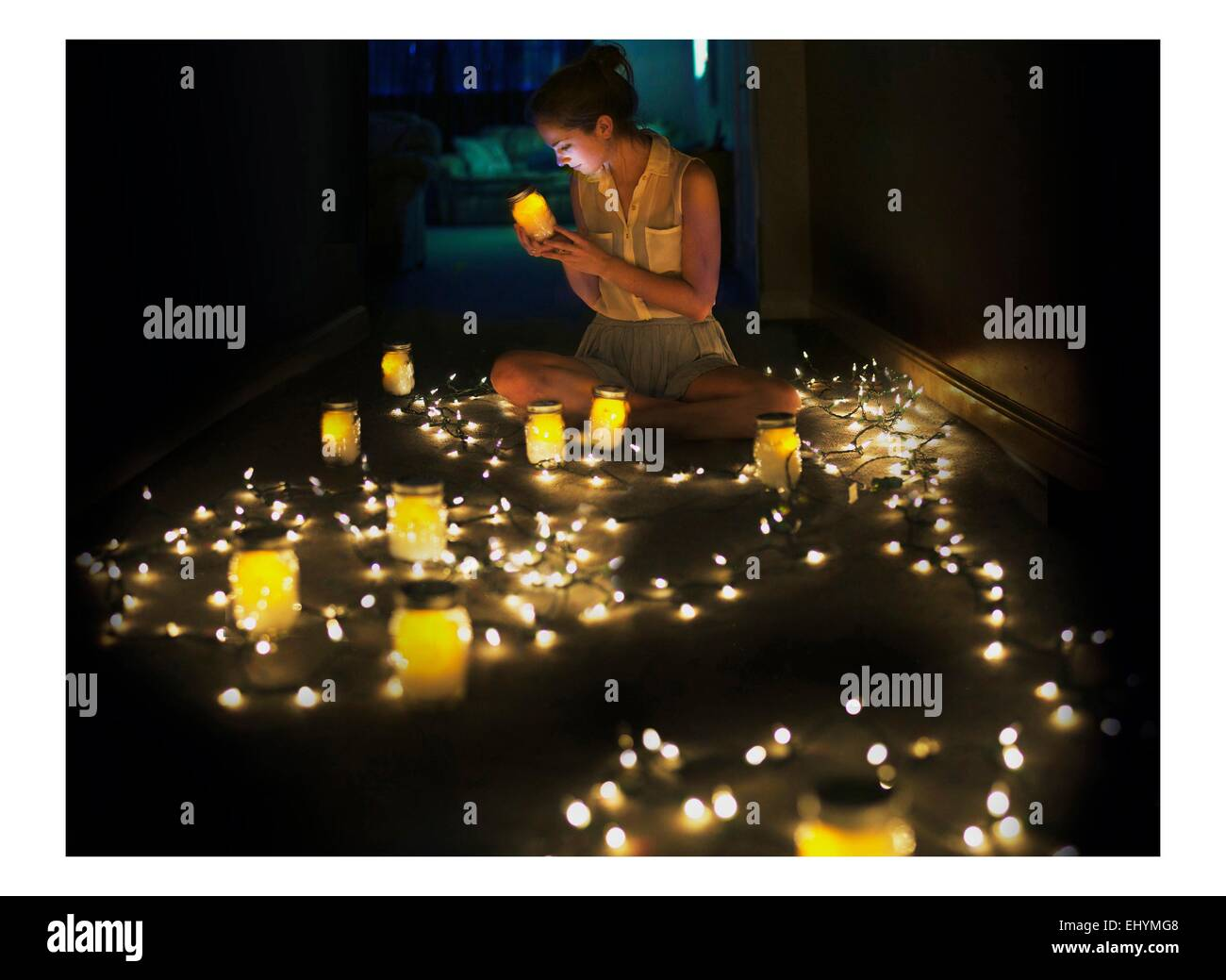Young woman sitting on floor surrounded by fairy lights and tea lights Stock Photo