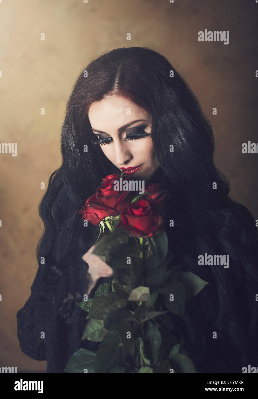 Portrait of a woman in black holding bunch of red roses - Stock Image