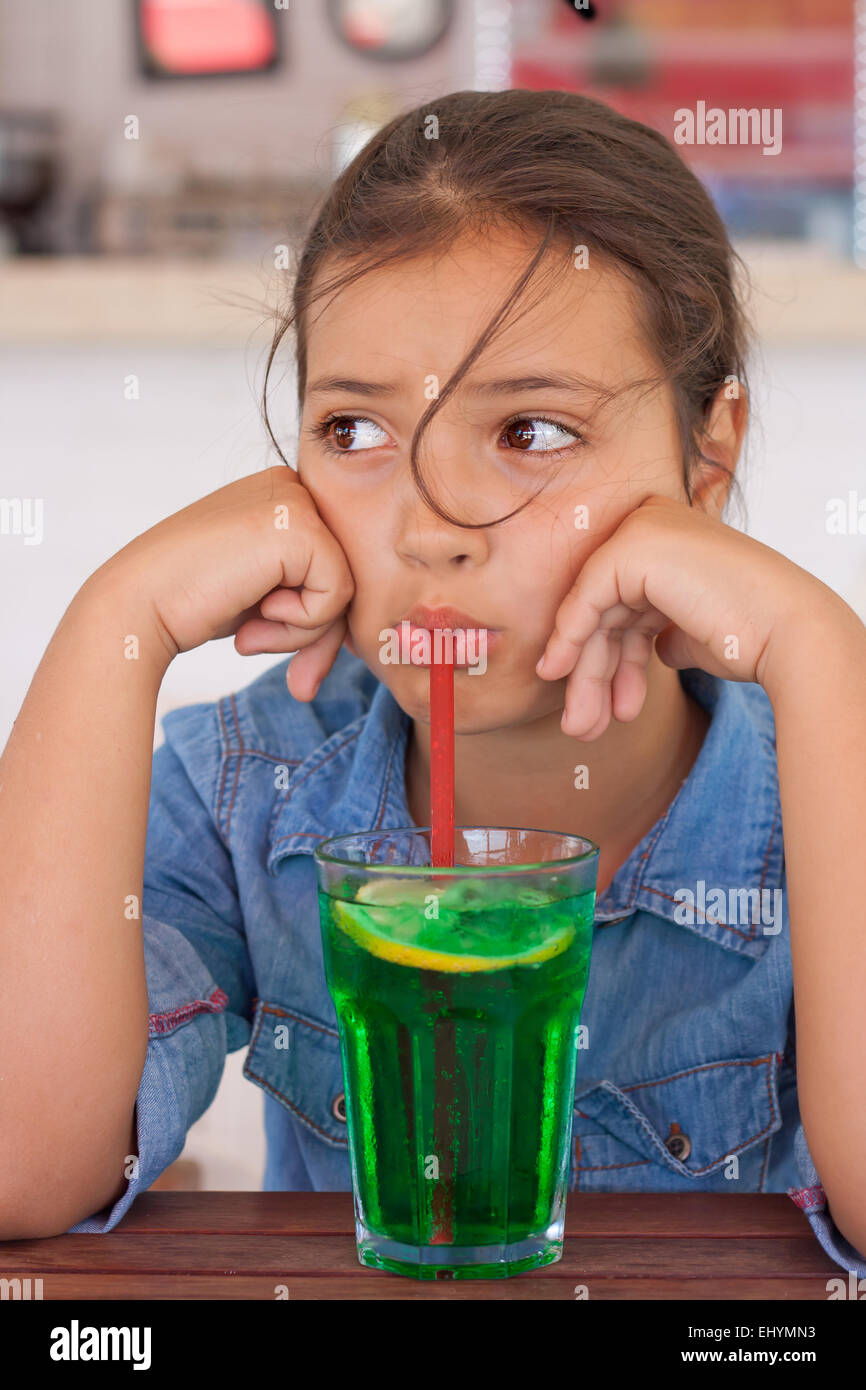 Grumpy girl drinking mocktail through a straw - Stock Image