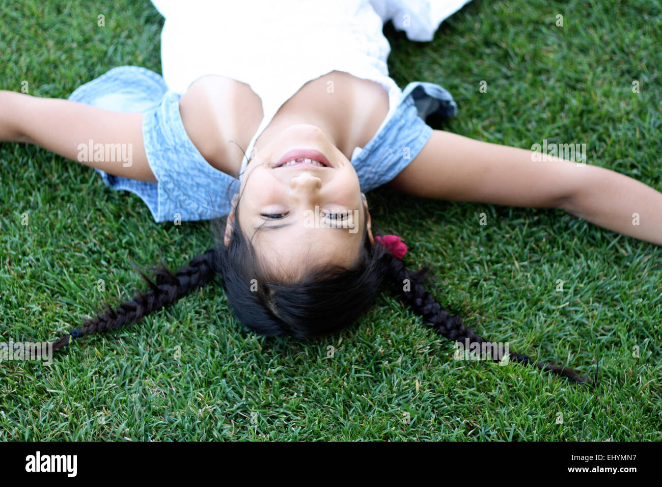 Upside down view of girl lying on grass - Stock Image