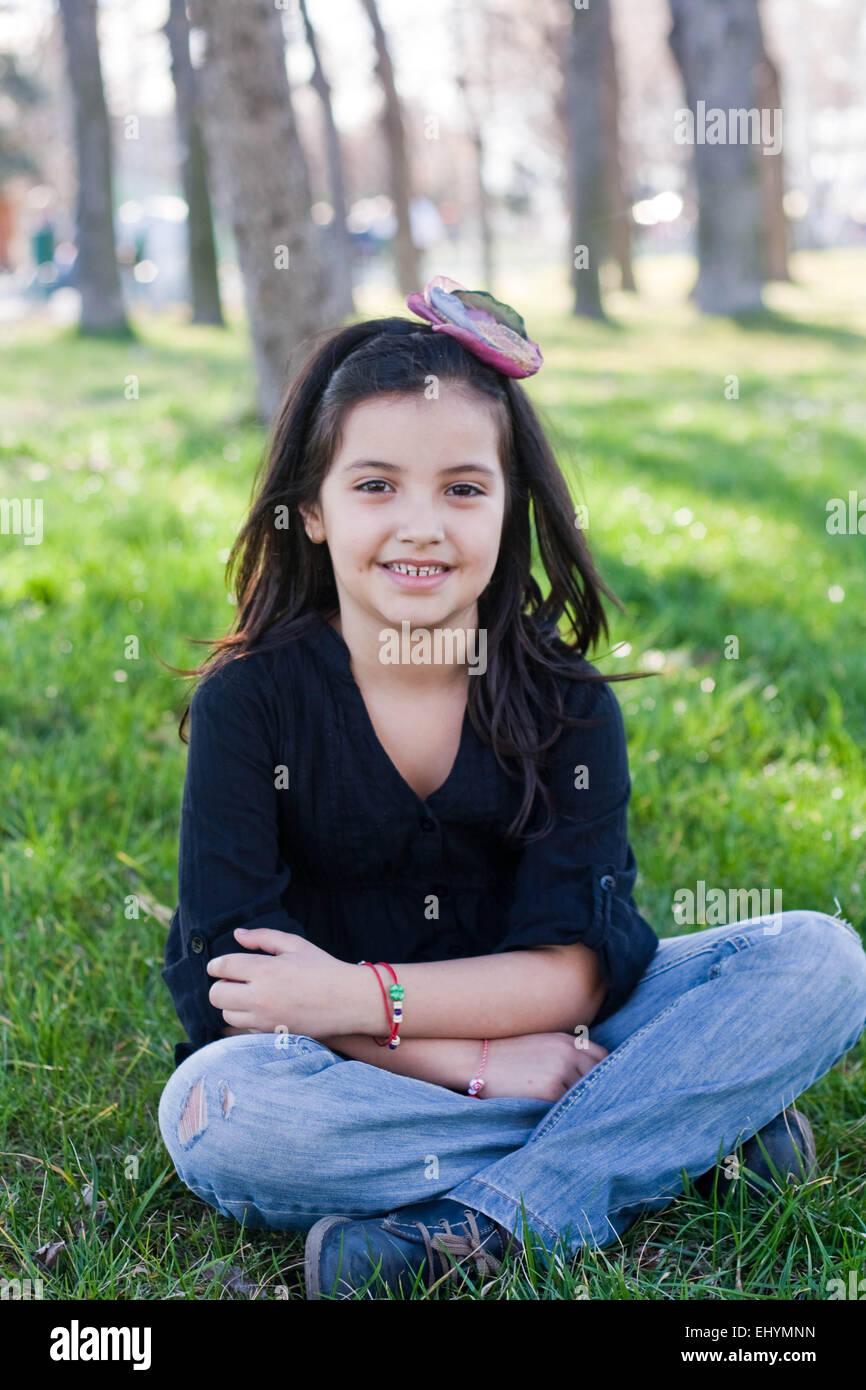 Smiling girl sitting cross-legged in the park - Stock Image
