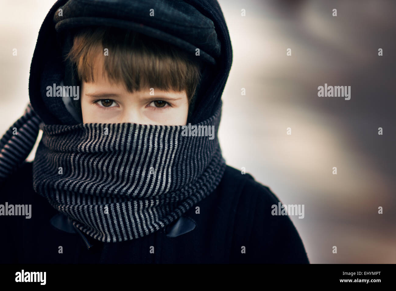 Boy wearing a scarf around his face - Stock Image