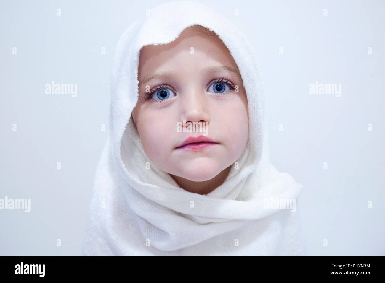 Portrait of a girl wearing a white headscarf - Stock Image