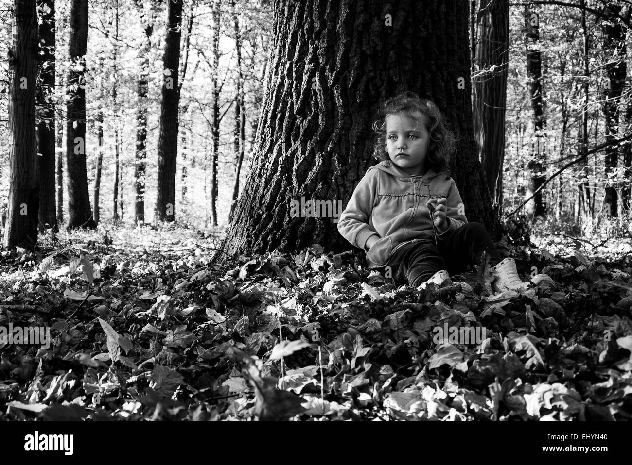 Girl sitting in the woods leaning against a tree trunk - Stock Image