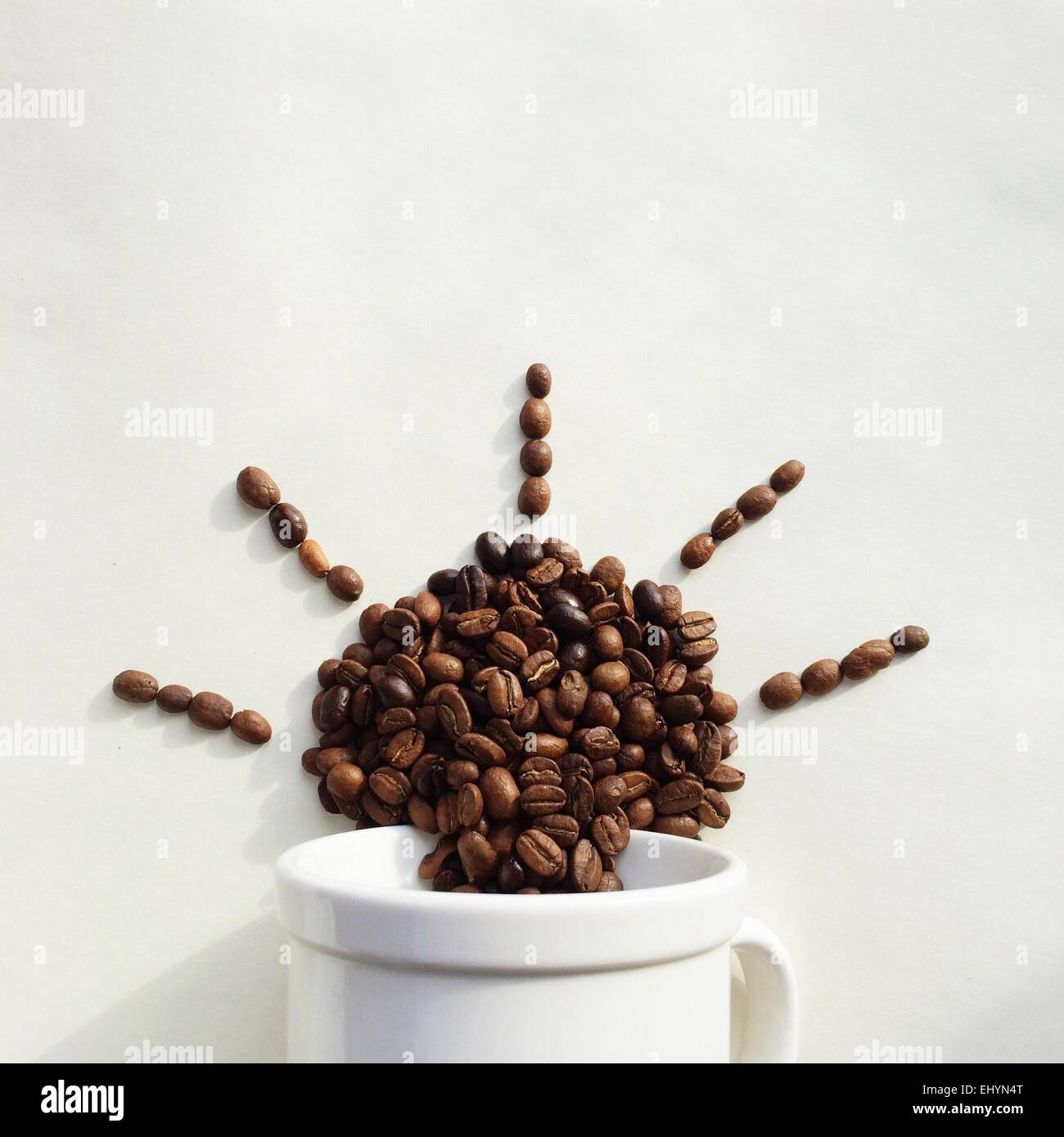 Coffee beans coming out of a cup in the shape of the sun - Stock Image
