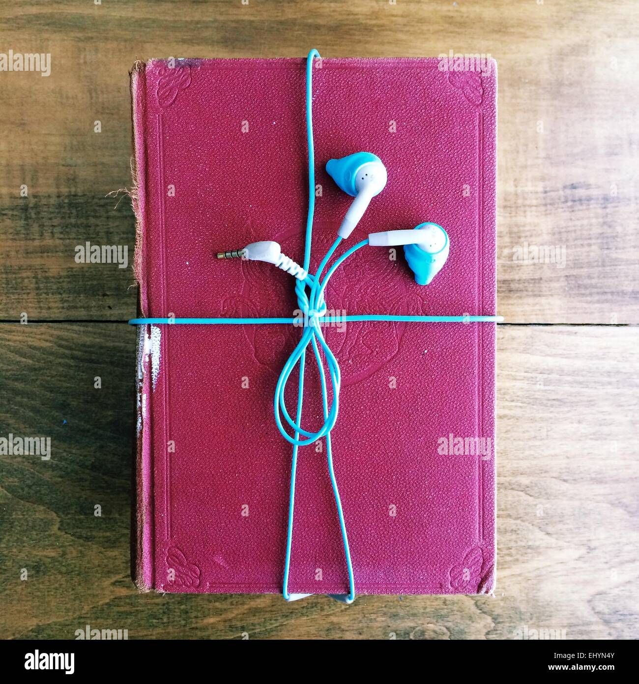 Headphones wrapped around an old book - Stock Image
