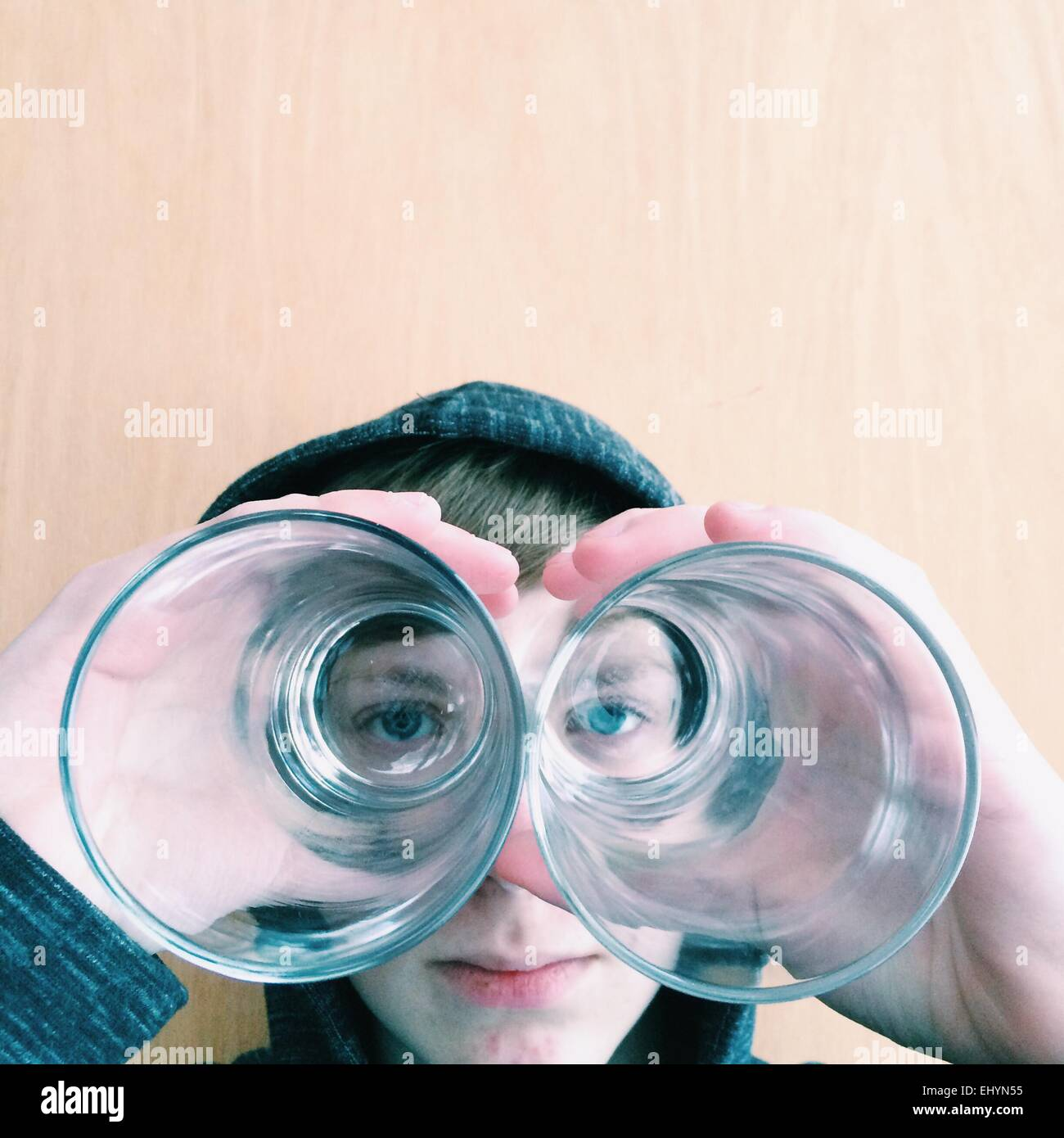 Boy looking through the bottom of two drinking glasses - Stock Image