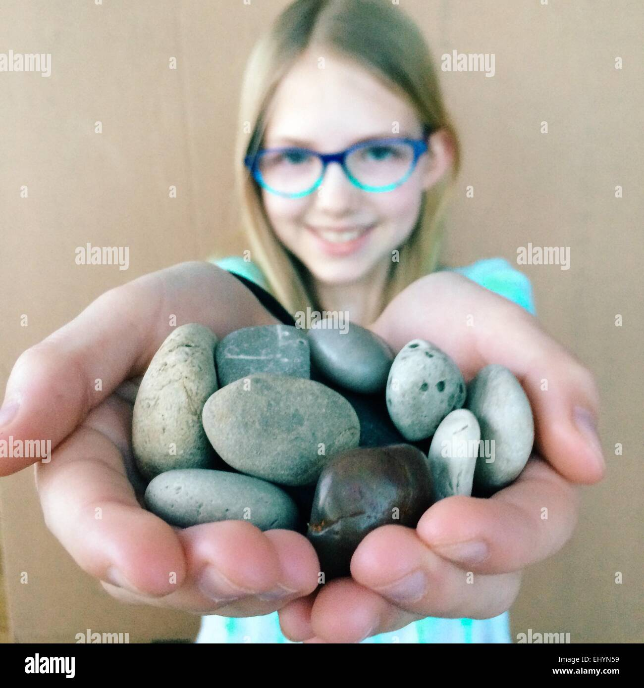 Girl holding a collection of rocks - Stock Image