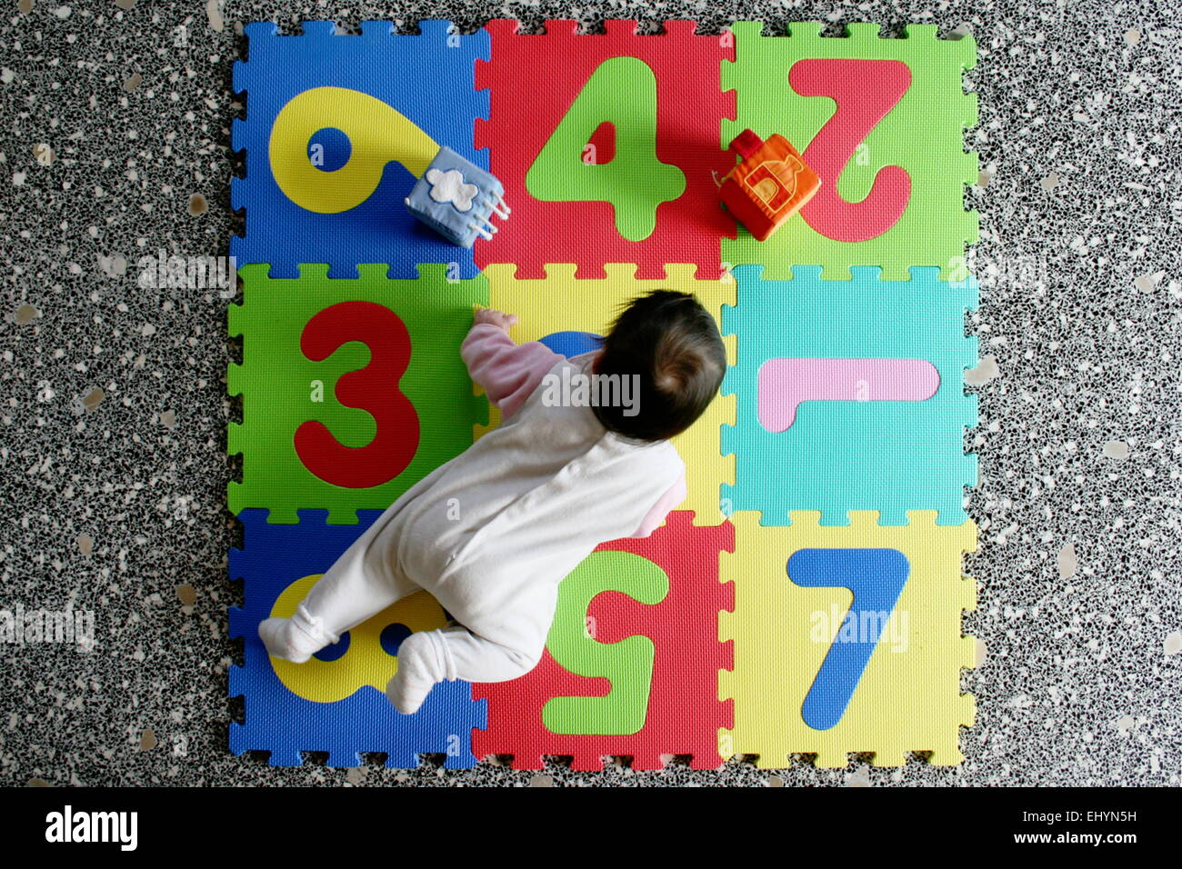 Baby girl in pink pyjamas playing with multi-colored toys - Stock Image