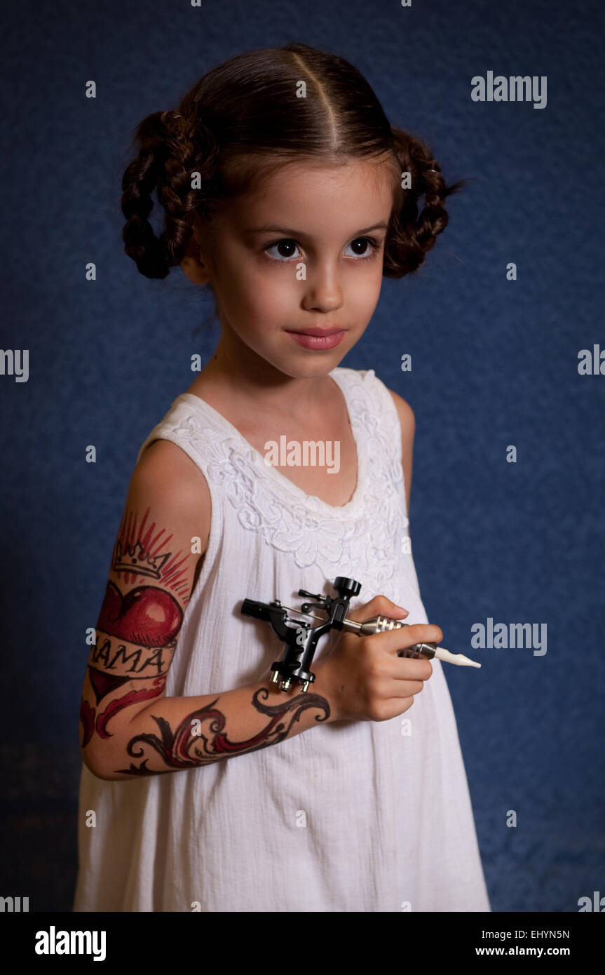 Angelic looking girl with a body painting holding a tattoo gun - Stock Image