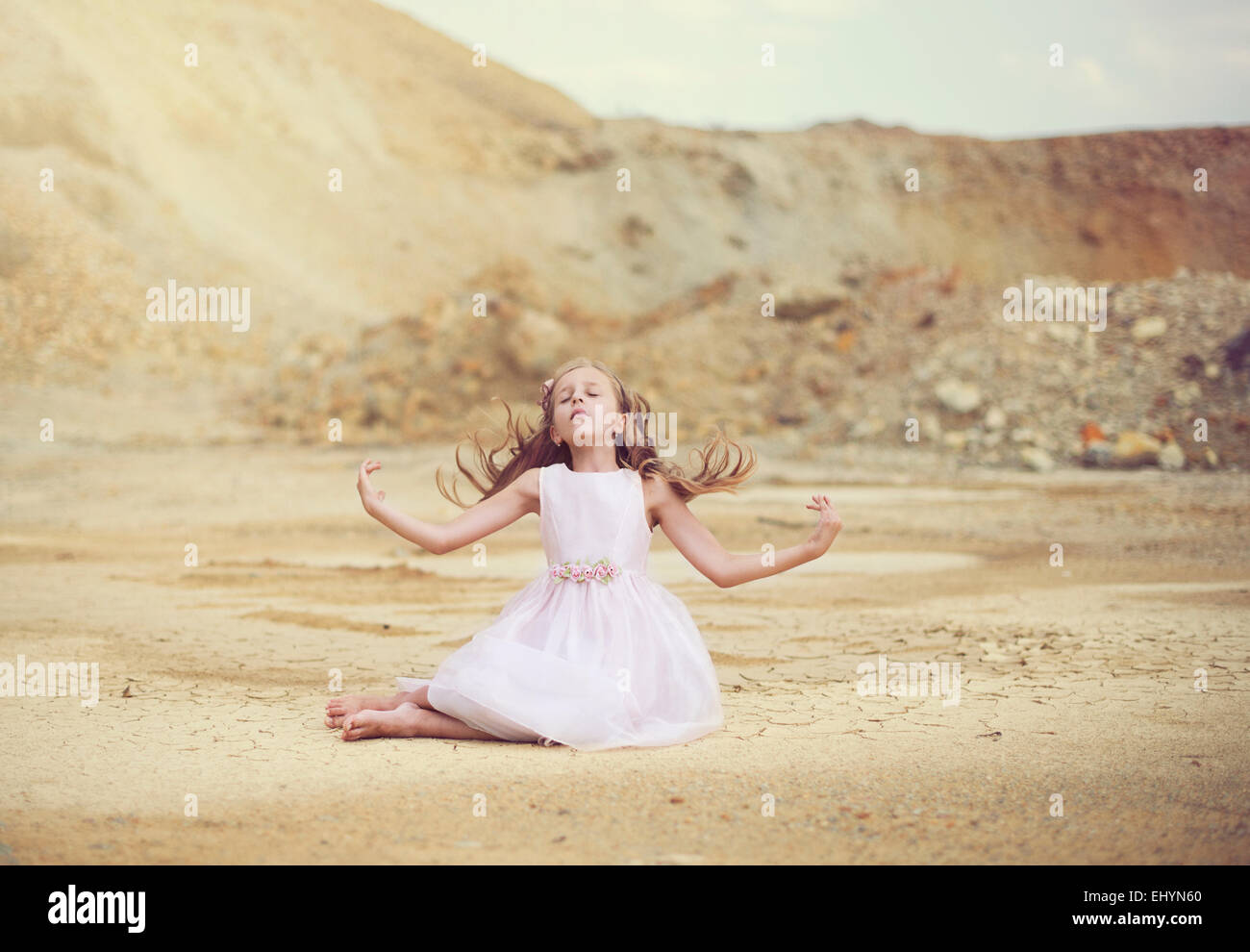 Girl sitting in the desert with her arms outstretched - Stock Image