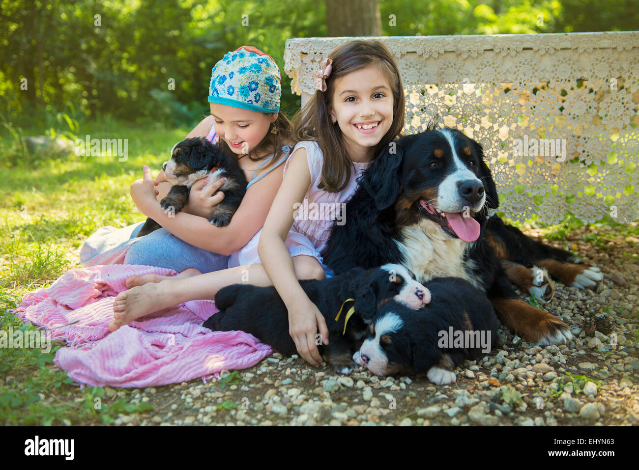 Two girls sitting in garden with a dog and puppies Stock Photo